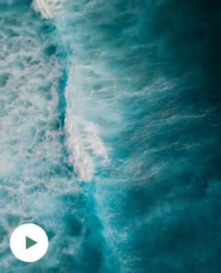 Symbolbild: Blick von oben auf Wellen und schäumendes, tiefes Wasser.